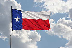 The Texas state flag flying on a beautiful day